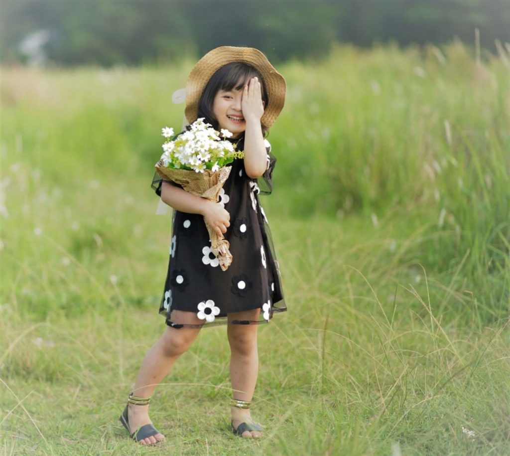sydney young asian girl with flowers and hat covering one eye in multifocal contact lenses or orthokeratology for myopia control
