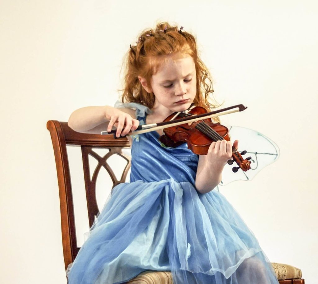young red headed girl playing violin on atropine eye drops for myopia management as option to orthokeratology in sydney